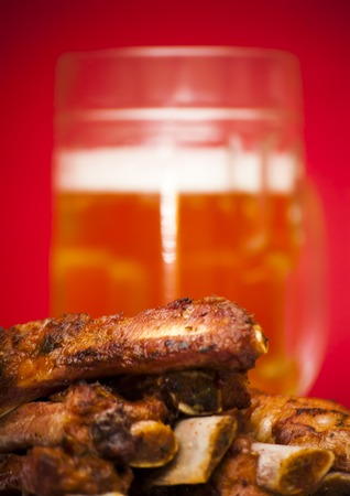 barbecues: Roasted pork ribs on a white plate with a pitcher of beer next