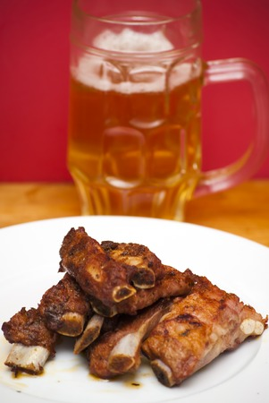 broil: Roasted pork ribs on a white plate with a pitcher of beer next