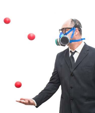 gas ball: Businessman with gas mask  that is juggling with a red balls over white