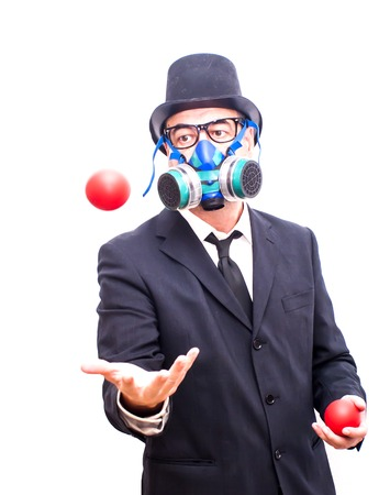 gas ball: Businessman with gas mask and hat  that is juggling with a red balls over white Stock Photo