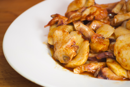 galician: Octopus with paprika and potatoes on a white plate, also known as Galician octopus, typical plate of Spain