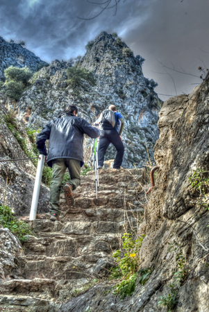 stair climber: Two mountaineers climb a stone staircase in the mountains Stock Photo
