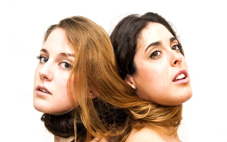 Portrait of two beautiful women back to each other in which they have hair tangled together on white background