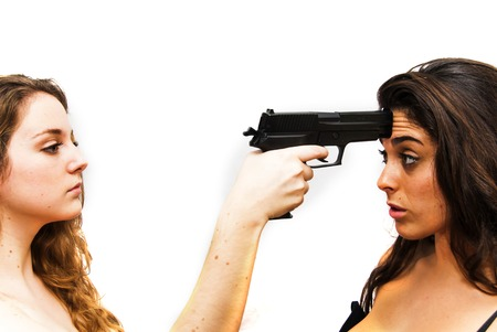 Portrait of two beautiful women, one opposite the other, in which a woman pointing a gun to the head of another woman on white background Banco de Imagens