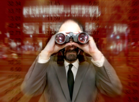 overexposed: Handsome business man, bald and bearad, looking through binoculars over   a background of an office building lit in the night and with a series of numbers overexposed