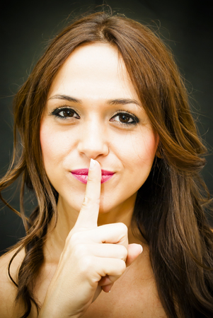 Portrait of a beautiful woman commanding silenced her with a finger gesture on lips on black background