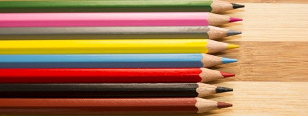 Colored pencils isolated on a wooden background Stock Photo