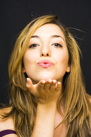 Portrait of a beautiful woman giving an air kiss on black background