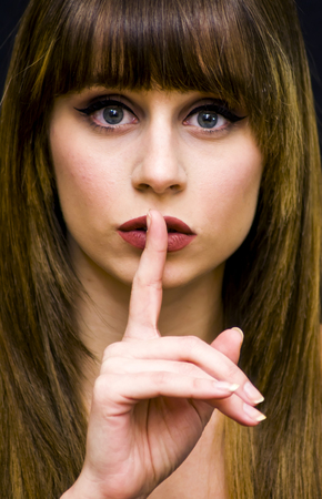 Beauty Woman Portrait  commanding silence with a finger gesture on her lips Isolated over Black Background
