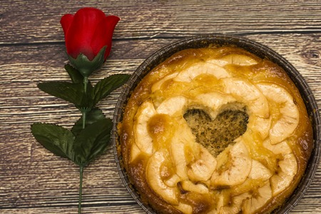 Apple pie with a hollow in the shape of a heart on a wooden table in which there is a red rose