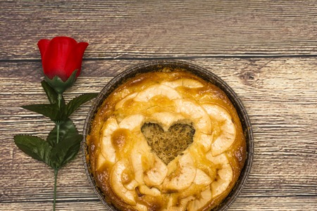 ocas: Apple pie with a hollow in the shape of a heart on a wooden table in which there is a red rose