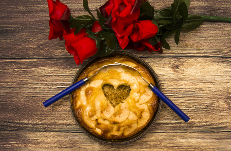 Apple pie with a hollow in the shape of a heart and two forks interlaced on a wooden table in which there is a bouquet of red roses