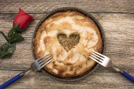 ocas: Apple pie with a hollow in the shape of a heart and two forks on a wooden table in which there is a red rose