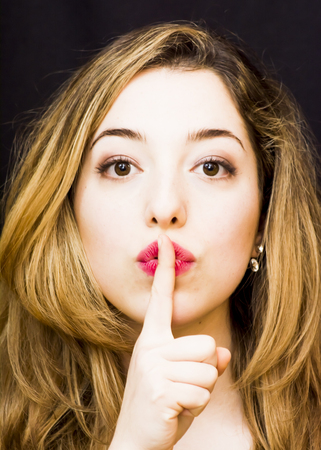 Beautiful woman commanding silence with a gesture of her finger index led to the lips over black Background
