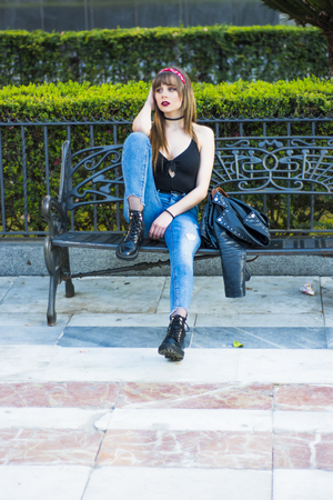 Portrait of a beautiful woman  on the street sitting on a bench Stock Photo