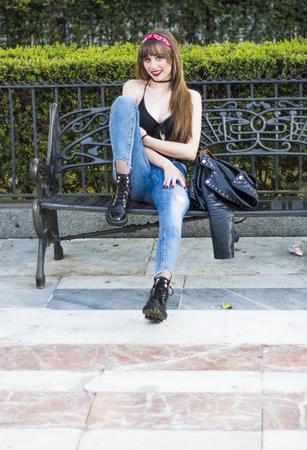 Portrait of a beautiful woman  on the street sitting on a bench 版權商用圖片
