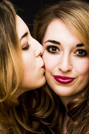 Two beautiful women  where one of them is giving a kiss on the cheek to the other Stock Photo