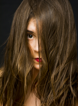 aging: Portrait of a beautiful woman  with her hair fallen on her face on black background Stock Photo