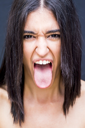 Portrait of a beautiful woman  with her tongue out of her mouth on black background