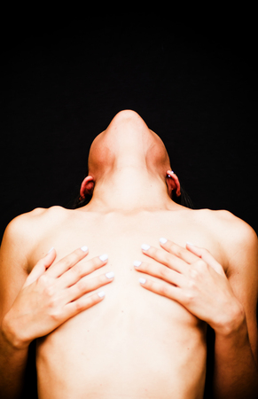Beautiful naked woman covering her breasts on black background Stock Photo