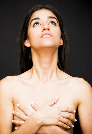 Beautiful topless woman covering her breasts on black background. Stock Photo