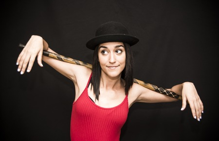 Portrait of a beautiful woman  with hat and cane on black background