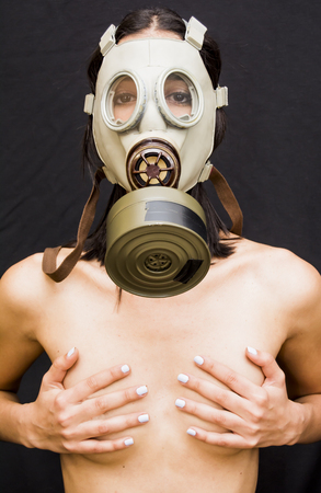 Beautiful naked woman  with gas mask covering her breasts on black background Stock Photo