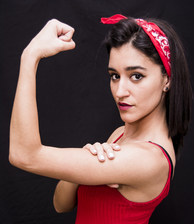 Portrait of a beautiful woman  with red scarf on her head making a gesture of strength on her arms on black background