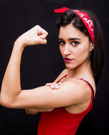 Portrait of a beautiful woman  with red scarf on her head making a gesture of strength on her arms on black background photo