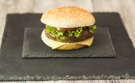 Delicious hamburger with cheese, lettuce and tomato on a stone