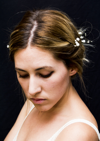 Portrait of a beautiful Woman with white flowers as a bride on her wedding day on black background