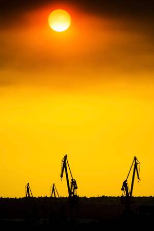 SEVILLE SPAIN - JUNE 25: Landscape of a cranes in a harbor at sunset with clouds on June 25 2017 in Seville, Andalusia, Spain.