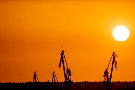 Landscape of a cranes in a harbor at sunset with clouds Stock Photo