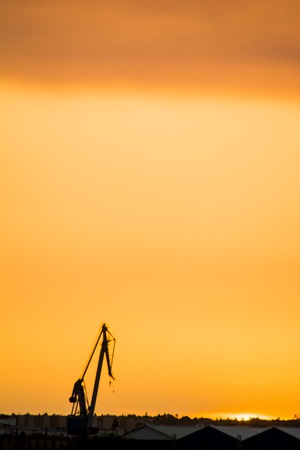 Landscape of a cranes in a harbor at sunset with clouds Фото со стока