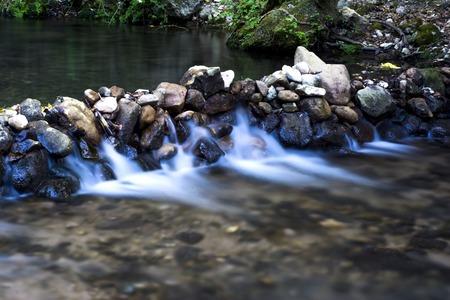 Landschap van een rivier met water loopt zijdeachtig, rotsen en bomen Stockfoto