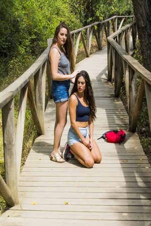 Two beautiful women, one of them arranges the hair to the other,  hiking in nature  on a wooden path in the mountains