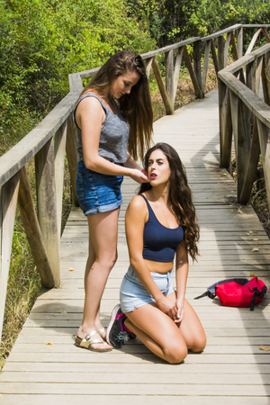 and hiking path: Two beautiful women, one of them arranges the hair to the other,  hiking in nature  on a wooden path in the mountains