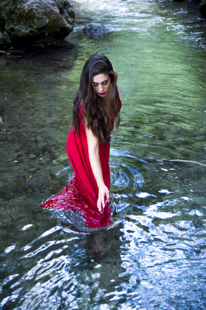 river banks: Beautiful woman on the bank of a mountain river with an evening dress