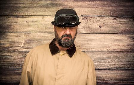 ひげ、ボウラー、レインコート、木製の背景でいくつかの奇妙な未来的な眼鏡の男 写真素材