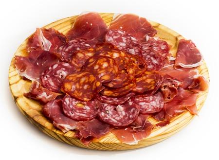 Comida típica española con jamón y salchicha en una placa de madera