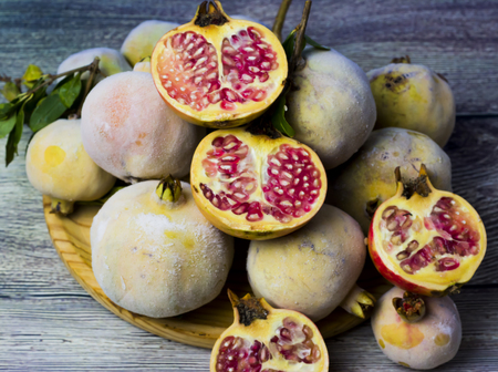 Pomegranate fruit on a wooden plate Imagens