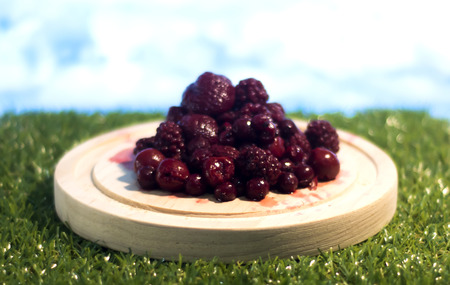 Forest fruits in a wooden dish on grass Archivio Fotografico