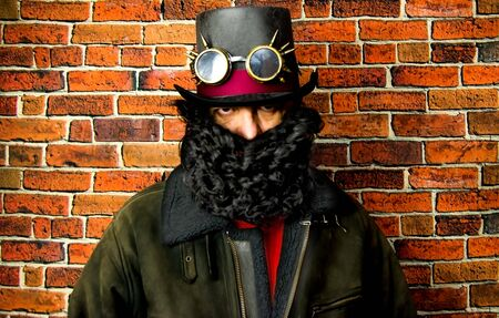Steampunk man with beard, hat and glasses on background of vintage brick wall