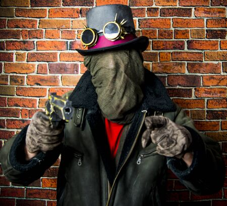 Steampunk man with gun, hidden face, hat and glasses on the background of vintage brick wall Banque d'images