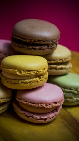 Colored macarons isolated on wooden dish, typical French dish
