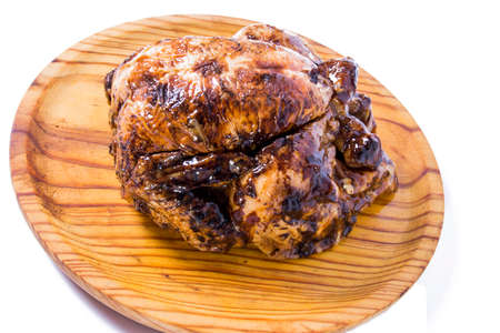 Roast chicken on a wooden tray on white background