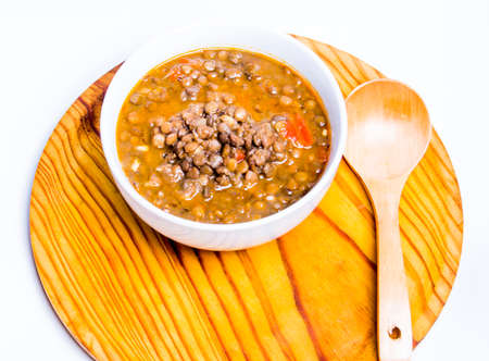 Tasty bowl of lentils on a wooden tray and white background