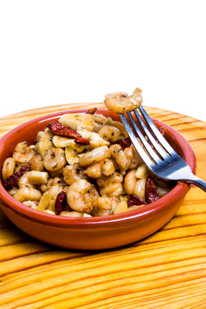 Tasty Prawns with garlic and cayenne in a ceramic bowl on a wooden tray