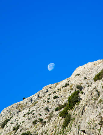 Montain landscape with the moon and blue sky