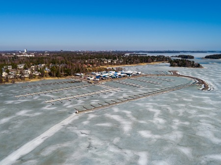 Finland Espoo, Nuottanimi marina on a spring day with water still in ice and the boats stored at land